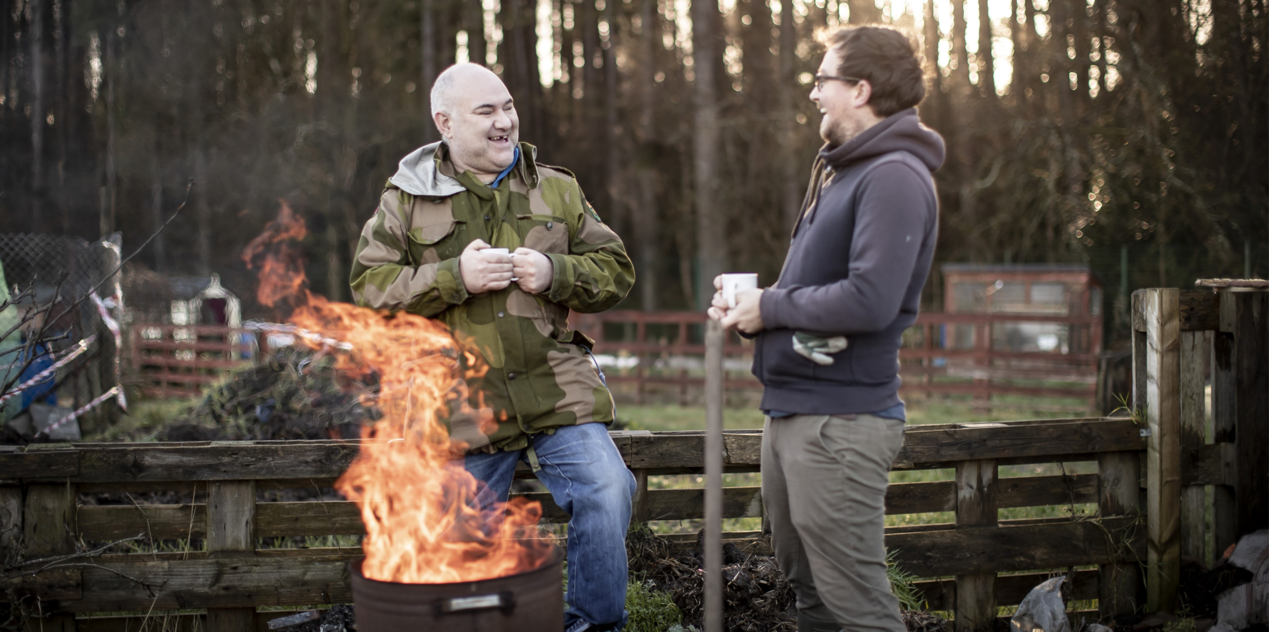 Two men laughing with each other by a fire