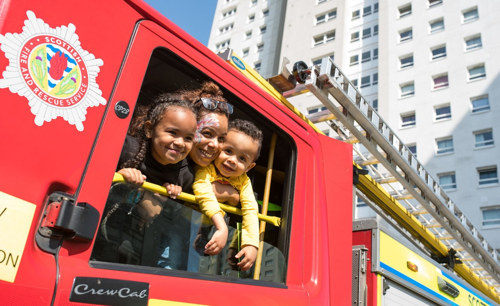 Three faces looking and smiling out the window of a fire engine
