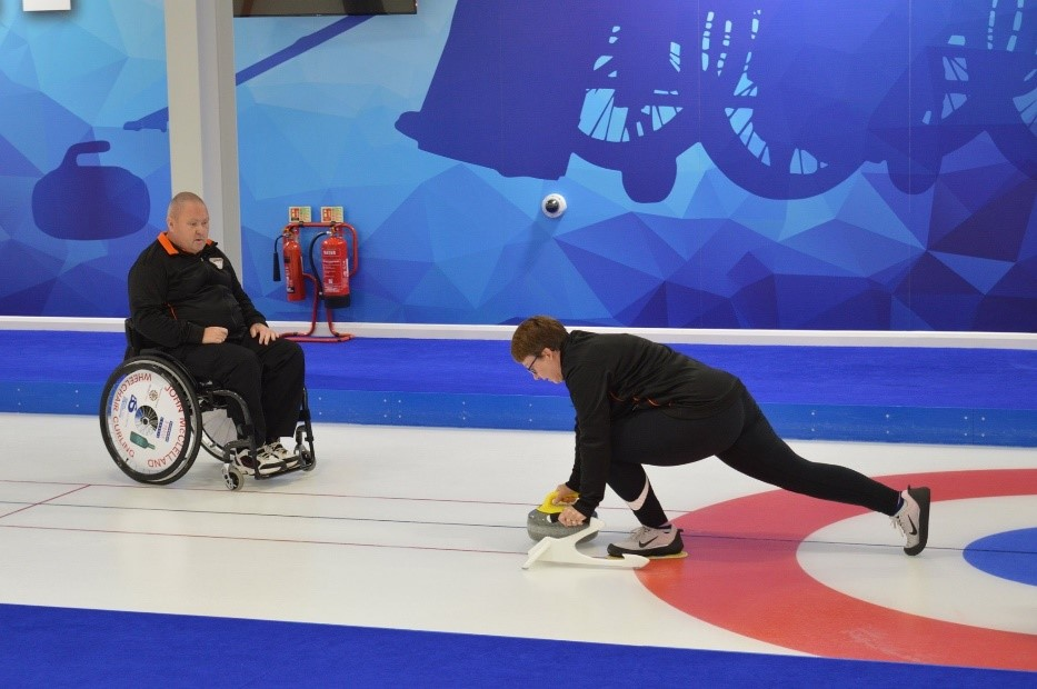 a man in a wheelchair teaching a woman how to play curling