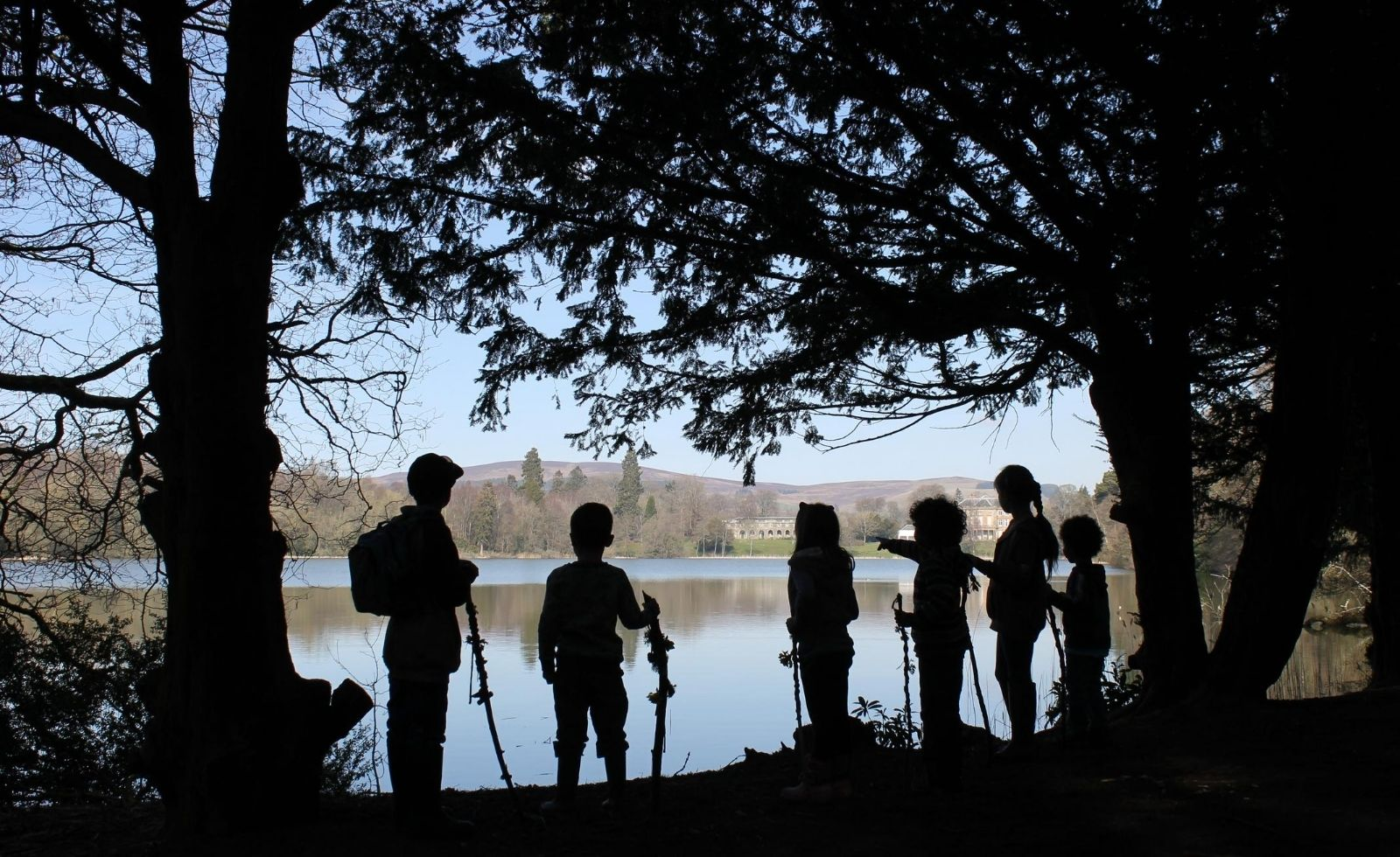 Silhouettes of children standing by the edge of a loch