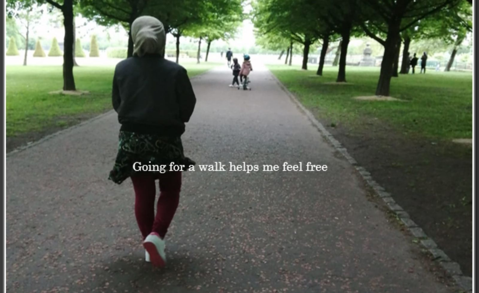 A women walking in the park. Her childing are playing further up the path.