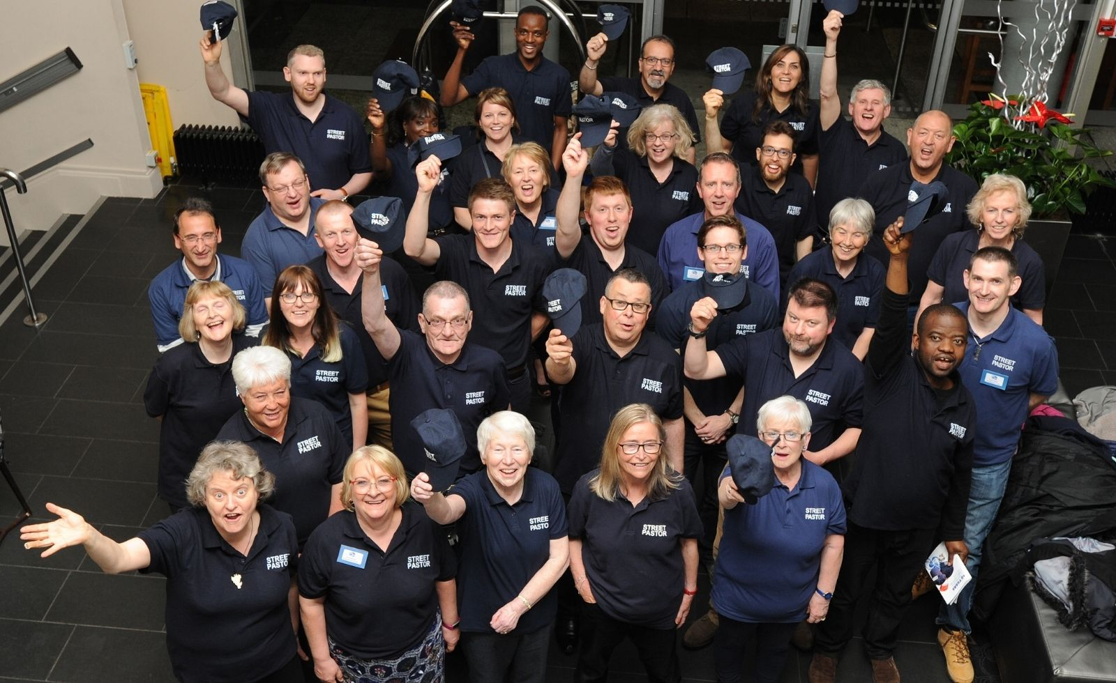A large group of street pastors all posing for the camera. Some are holding dark blue caps in the air.
